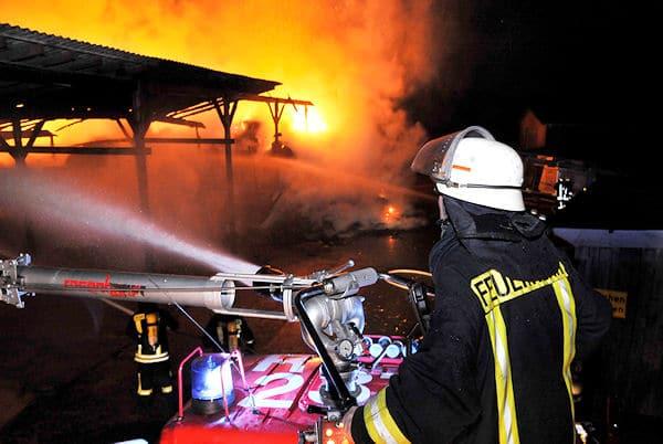 Per Wasserwerfer wird der brennende Reiterhof in Marl gelöscht. Foto: Guido Bludau