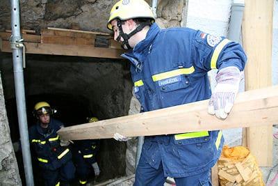 THW-Helfer bringen Stützholz in den Keller eines Hauses in Asperg. Foto: Benjamin Beytekin