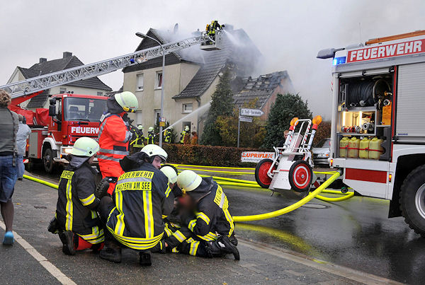 Einsatzkräfte kümmern sich um den zusammengebrochenen Feuerwehrmann. Foto: Guido Bludau
