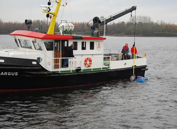 """Das Hafenaufsichtsboot """"Argus"""" der Niedersachsen Ports hebt mit seinem Kran das Unfallfahrzeug. Foto: Polizeiinspektion Wilhelmshaven/Friesland"""