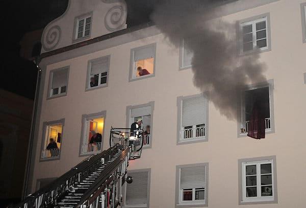 Qualm dringt aus einer brennenden Küche in Altötting, Bewohner stehen an den Fenstern. Foto: fib / Shooteragentur