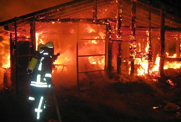 Unter Atemschutz beginnt ein Trupp mit den Löscharbeiten. Foto: Thomas Reiff / Feuerwehr