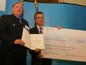 Thomas de Maizière (re.) übergibt Helmut Görges von der FF Kettwig Siegerurkunde und einen symbolischen Scheck. Foto: Sönke Jacobs / DFV