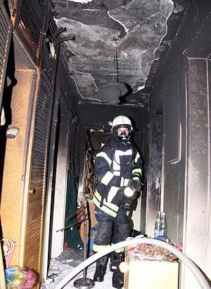 Ein Atemschutzgeräteträger in der ausgebrannten Wohnung. Foto: Timo Jann