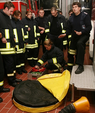 Kai Jansen (rechts) zeigt den Feuerwehranwärtern, wie die Hebekissen funktionieren. Foto: Lina Timm