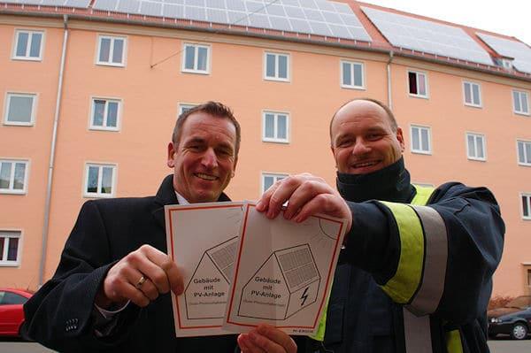 Volker Skrok, Leitender Branddirektor der Berufsfeuerwehr Nürnberg (rechts), und Thomas Fösel, Geschäftsführer der impleaPlus GmbH, präsentieren die Kennzeichnungsaufkleber. Foto: N-Ergie
