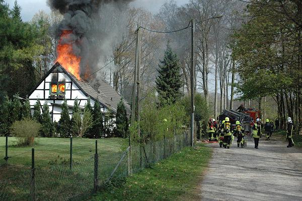 Flammen schlagen aus dem Dachstuhl, die Feuerwehr bereitet gerade einen Drehleitereinsatz vor. Foto: Feuerwehr Ratingen