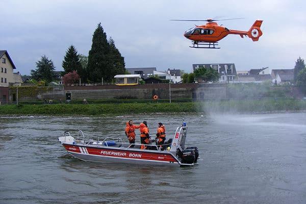 """Rettungshubschrauber """"Christoph 3"""" und ein Mehrzweckboot der Feuerwehr Bonn eilen einem Mann im Rhein zur Hilfe. Foto: Feuerwehr Bonn"""
