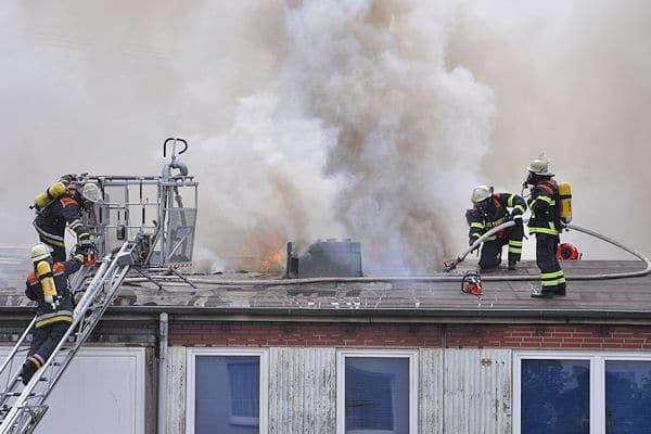 Brandbekämpfung auf einem Hochhausdach: Die Löscharbeiten dürfen aufgrund der Rauchentwicklung nur unter Atemschutz erfolgen. Foto: Mundt