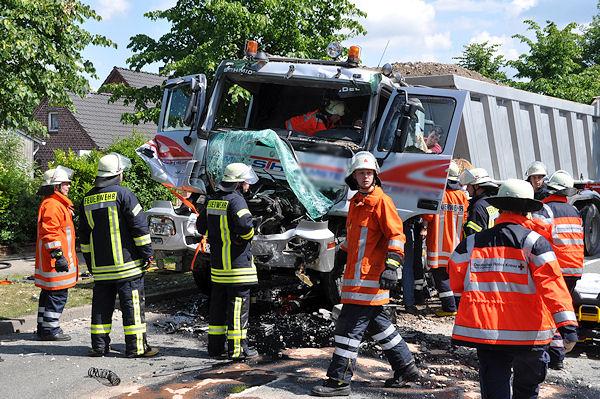 Feuerwehrleute und Rettungsdienstmitarbeiter bemühen sich um den eingeklemmten Lkw-Fahrer in Agathenburg. Foto: Polizei Stade