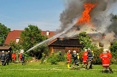 Ein Dachstuhl brennt in Grödig bei Salzburg (Österreich). Im Gebäude lagern Feuerwerkskörper. Foto: Schweiger