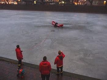 Eisrettung in Bremen: Ein Feuerwehrmann geht mit einem Eisrettungsschlitten vor, um einen Ball zu bergen. Foto: Polizei