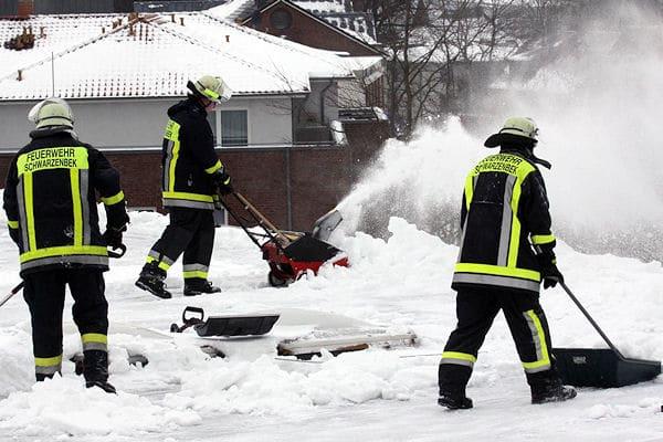 Schneedruck auf dem Dach: Die Feuerwehr räumt Schnee von einem Flachdach (Februar 2010). Foto: Timo Jann