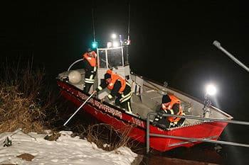 Feuerwehrleute suchen von einem Boot aus nach dem Vermissten. Foto: Ralf Hettler