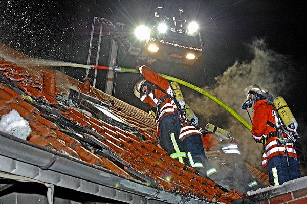 Unter Atemschutz führen Feuerwehrleute Nachlöscharbeiten auf dem Dach durch. Foto: Stephan Konjer
