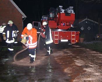 Feuerwehrleute streuen Ölbindemittel auf eine vereiste Zufahrt. Erst danach gelingt es dem Maschinisten, die Drehleiter in Stellung zu bringen. Foto: Thomas Weege