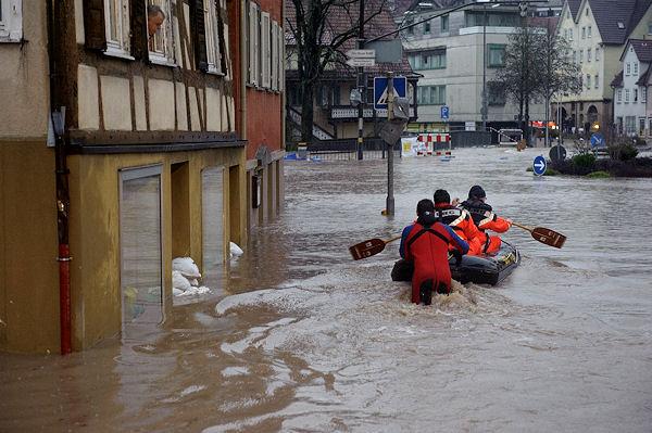 DLRG-Helfer fahren mit einem Schlauchboot auf einer Straße in Backnang, um eingeschlossene Gäste eines Hotels zu befreien. Ein Anwohner beobachtet die Szene aus dem Fenster. Foto: Oskar Eyb