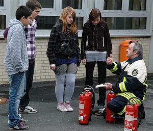 Zur praktischen Ausbildung gehörte auch der richtige Umgang mit Feuerlöschern, den der stellvertretende Kreisbrandinspektor Jörg Fackert erklärte und zeigte. Foto: Landkreis Marburg-Biedenkopf