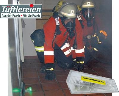 """Mit dem grün blinkenden """"Notfallkeil"""" (links) sichert der Atemschutztrupp die Tür. So findet er auch bei Rauch und Dunkelheit zurück."""