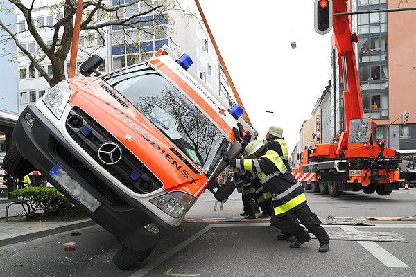Mit Kranunterstützung und Muskelkraft stellt die Feuerwehr München einen verunfallten Rettungswagen zurück auf die Räder. Foto: BF München