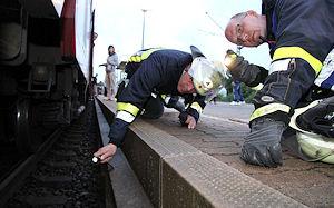 Feuerwehrleute kontrollieren im Bahnhof Schwarzenbek nach einer Rauchentwicklug einen Zug. Foto: Timo Jann