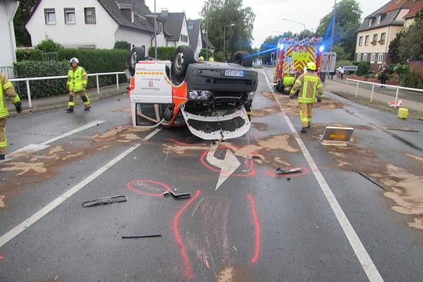 Feuerwehrleute streuen nach dem Unfall mit einem Notarzteinsatzfahrzeug in Ratingen ausgelaufene Betriebsstoffe ab. Foto: Polizei