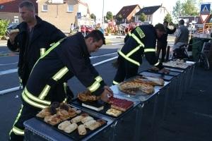 Süße Einsatzstellenversorgung: Einsatzkräfte bedienen sich an einem Kuchenbuffet bei einem Brand in einer Bäckerei. Der Besitzer hat das Buffet extra für die Helfer aufbauen lassen. Foto: Thomas Weege