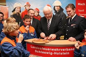 Ministerpräsident Peter Harry Carstensen schneidet die erste Feuerwehr-Mettwurst an: Foto: Bauer/LFV SH