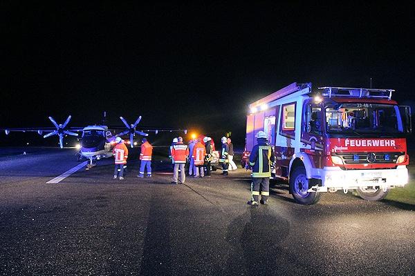 Feuerwehrkräfte stehen am Flugplatz neben der notgelandeten Dornier DO-228. Foto: Stürenburg/Feuerwehr