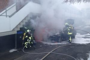 Ein Angriffstrupp löscht einen brennenden Pkw an einem Mehrfamilienhaus. (Foto: Feuerwehr Scharbeutz)