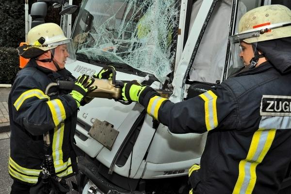 Mitglieder der Feuerwehr Nordhorn entfernen mit einem Spreizer die Fahrertür eines verunfallten Lkw. Anschließend kann der eingeklemmte Fahrer befreit werden. (Foto: Stepahn Konjer)