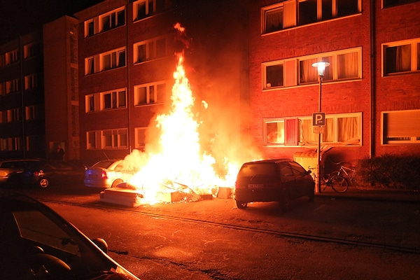 Archivfoto vom April 2013 - es handelt sich nicht um den Brand in Bremerhaven, sondern um einen ähnlichen Vorfall in NRW: Ein Sperrmüllhaufen brennt nachts vor einem Gebäude in Düren. Foto: Polizei