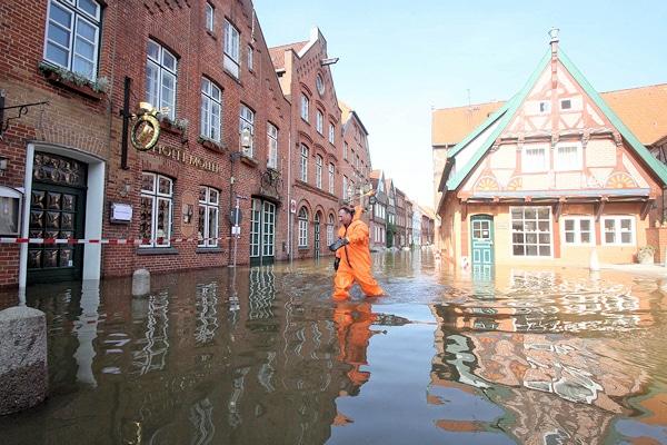 Die Elbstraße in Lauenburg steht jetzt bereits in weiten Teilen unter Wasser. Feuerwehrleute arbeiten daran, die Lage unter Kontrolle zu bringen. Foto: Timo Jann