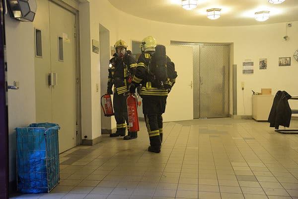 Einsatzkräfte vor dem verrauchten Gebäudeteil. Foto: Feuerwehr