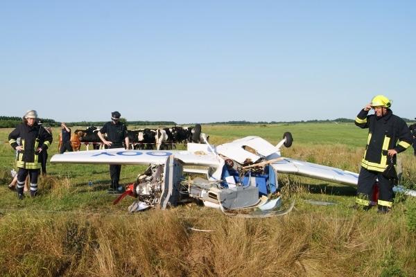 Ein Kleinflugzeug liegt nach einer missglückten Notlandung total zerstört auf einer Kuhweide in der Nähe des Emder Flugplatzes. Foto: Joachim Riese