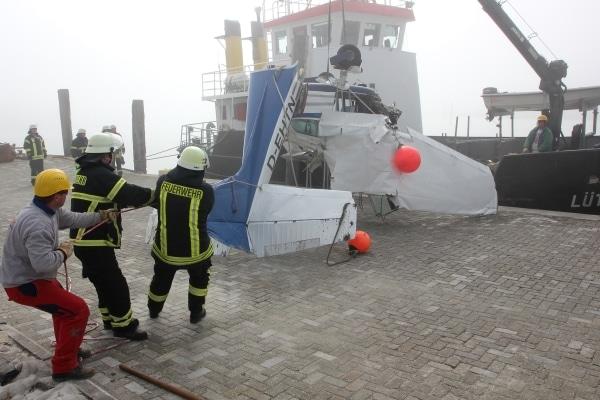 Feuerwehrleute unterstützen im Norddeicher Hafen die finale Bergung der zuvor im Wattenmeer abgestürzten Cessna. Foto: Thomas Weege