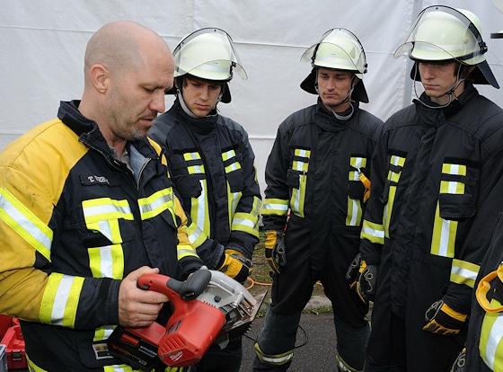 Feuerwehr-Ausbildung: Ausbilder Thorsten Weber erklärt den Neulingen Timo Lahr, Frank Höhne und Ralf Trump (v.l.n.r.) Technik und Funktion der elektrischen Akku-Kreissäge. Foto: Scheer