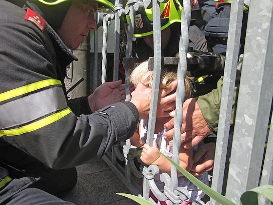 Ein Kind steckt im Zaun fest. Behutsam retten Feuerwehrleute das Mädchen. Foto: Kollinger