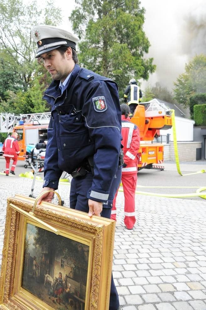 EIn Polizist trägt ein Gemälde aus der brennenden Villa. Foto: KDF-Television & Picture Germany