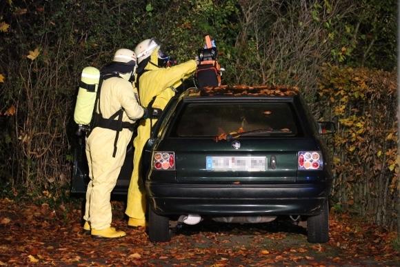 Gefahrguteinsatz nach Suizid: Einsatzkräfte nähern sich mit Schutzanzügen einem Toten in einem Pkw. Foto: Mario Avenia