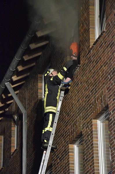 Ein Feuerwehrmann betreut die Frau von außen, während der Angriffstrupp ihr eine Fluchthaube aufsetzt. Foto: Preuschoff
