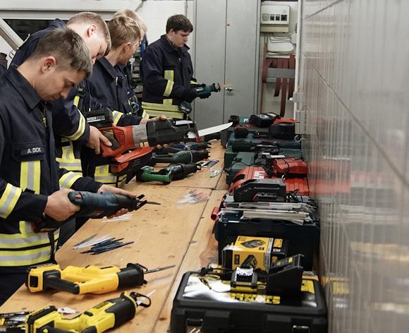 Säbelsäge bei der Feuerwehr: Die Tester bestücken die Geräte. Foto: Hegemann