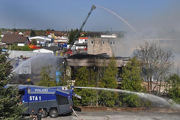 Drehleiter und Wasserwerfer der Polizei bei Löscharbeiten während eines Großbrandes. Foto: Andreas Rosar Fotoagentur-Stuttgart