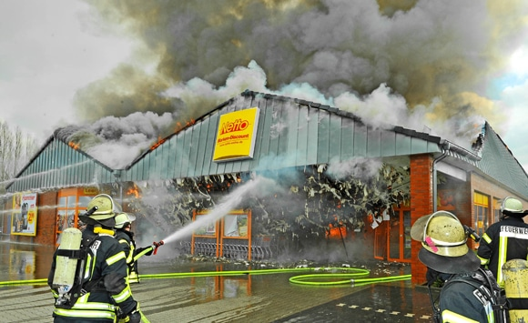 Einsatzkräfte während der Löscharbeiten bei einem Supermarktbrand in Nordhorn. Foto: Konjer