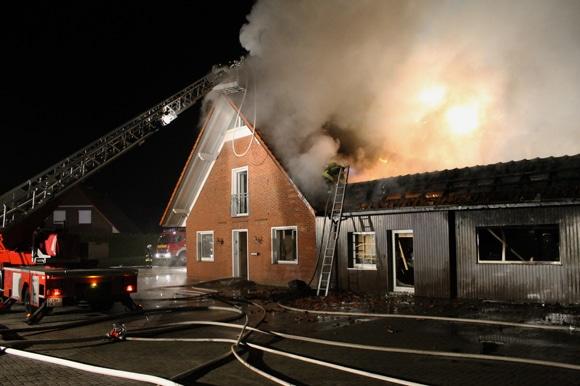 Flammen treten aus dem Dachstuhl eines Wohnhauses aus. Autohaus -Brand in Twistringen. Foto: Kreisfeuerwehr Diepholz / Thom