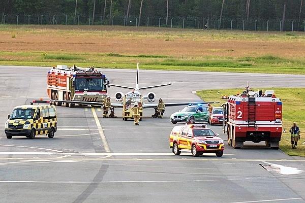 Kräfte der Feuerwehr sichern die Maschine während sie vom Rollfeld gezogen wird. Foto: News5 / Linschmann