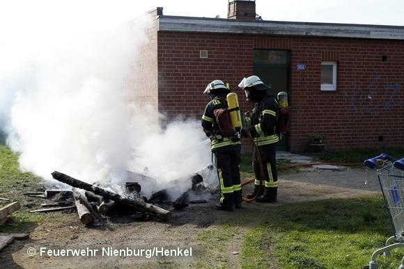 Nienburger Feuerwehrleute löschen einen Holzstapel, der direkt neben einem Gebäude angezündet worden war. Foto: Feuerwehr Nienburg/Henkel