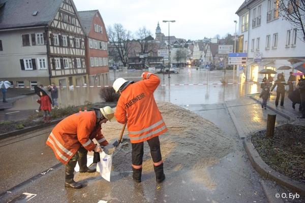 Hochwasser in Backnang, ein Laster kippte zwei Ladungen Sand in die Asbach (oder so ähnlich) Strasse, Feuerwehrleute befuellten Sandsäcke damit