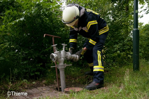Ein Feuerwehrmann bringt an einem Standrohr einen Systemtrenner BA an. Foto: Thieme