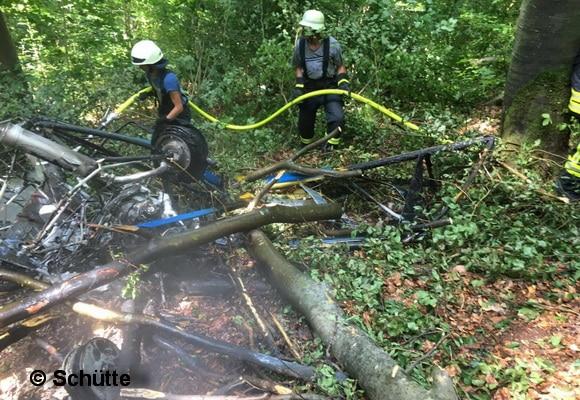 Nachlöscharbeiten am Ultraleichtflugzeug durch Feuerwehrleute am Waldboden. Foto: Schütte